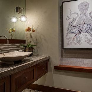 Foto di un bagno di servizio tropicale con ante in stile shaker, ante in legno scuro, lavabo a bacinella, top in travertino e top marrone