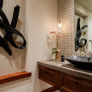 Idées déco pour un WC et toilettes exotique avec un placard avec porte à panneau encastré, des portes de placard en bois brun, un WC à poser, carrelage en mosaïque, un sol en galet, une vasque et un plan de toilette en travertin.