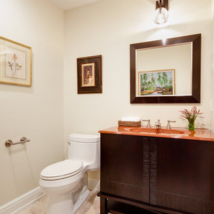 Photo of a medium sized traditional cloakroom in New York with freestanding cabinets, dark wood cabinets, a one-piece toilet, beige walls, porcelain flooring, an integrated sink and orange worktops.