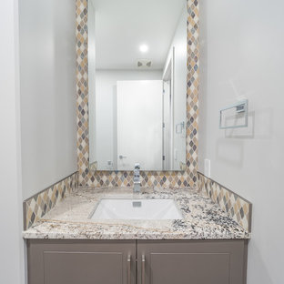 Photo of a medium sized contemporary cloakroom in Edmonton with beaded cabinets, grey cabinets, multi-coloured tiles, stone tiles, quartz worktops, a two-piece toilet, grey walls, vinyl flooring, a built-in sink and multi-coloured floors.