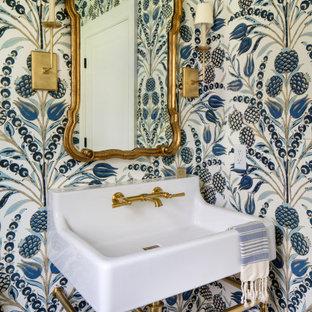 Bild på ett litet maritimt vit vitt toalett, med ett urinoar, blå väggar, mellanmörkt trägolv, ett piedestal handfat och brunt golv
