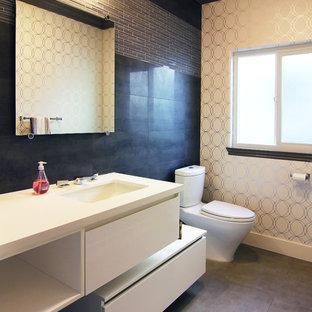 Inspiration pour un petit WC et toilettes design avec un lavabo encastré, un placard à porte plane, des portes de placard blanches, un plan de toilette en quartz modifié, un WC séparé, un mur noir, un sol en carrelage de porcelaine, un carrelage gris et des carreaux en allumettes.