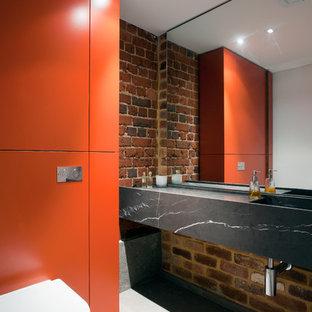 На фото: туалет среднего размера в стиле лофт с монолитной раковиной, плоскими фасадами, оранжевыми фасадами и мраморной столешницей с