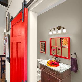 Ejemplo de aseo contemporáneo, de tamaño medio, con lavabo sobreencimera, armarios con paneles empotrados, sanitario de dos piezas, paredes grises, suelo de madera oscura, encimera de granito y puertas de armario de madera en tonos medios