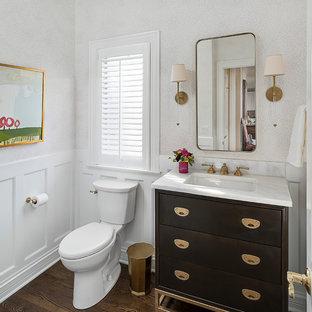 Foto de aseo clásico renovado, pequeño, con armarios con paneles lisos, puertas de armario de madera en tonos medios, lavabo bajoencimera, encimera de mármol, suelo marrón, sanitario de dos piezas, paredes blancas y suelo de madera oscura