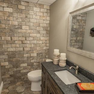 デトロイトの中くらいのおしゃれなトイレ・洗面所 (落し込みパネル扉のキャビネット、中間色木目調キャビネット、ベージュの壁、アンダーカウンター洗面器、マルチカラーの床、グレーの洗面カウンター、造り付け洗面台、レンガ壁) の写真