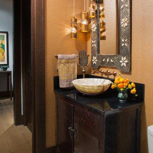 デンバーの小さいエクレクティックスタイルのおしゃれなトイレ・洗面所 (フラットパネル扉のキャビネット、茶色いキャビネット、オレンジの壁、セメントタイルの床、ベッセル式洗面器) の写真