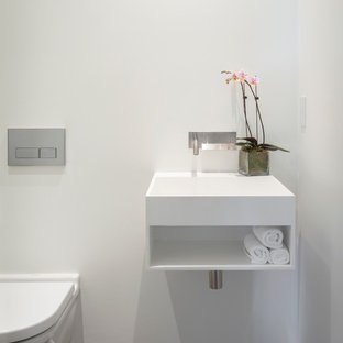 Inspiration for a contemporary powder room remodel in San Francisco with a wall-mount sink, open cabinets, white cabinets and a wall-mount toilet
