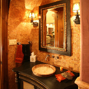 Large mediterranean cloakroom in Austin with freestanding cabinets, black cabinets, mosaic tiles, brown walls, a vessel sink, wooden worktops and orange tiles.