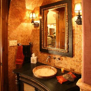 Modelo de aseo mediterráneo, grande, con armarios tipo mueble, puertas de armario negras, baldosas y/o azulejos en mosaico, paredes marrones, lavabo sobreencimera, encimera de madera y baldosas y/o azulejos naranja