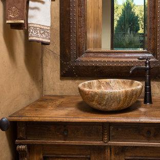 他の地域の小さいラスティックスタイルのおしゃれなトイレ・洗面所 (ベッセル式洗面器、家具調キャビネット、木製洗面台、濃色木目調キャビネット、ブラウンの洗面カウンター) の写真