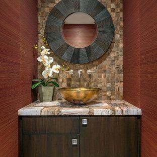 Новый формат декора квартиры: туалет в современном стиле с настольной раковиной, плоскими фасадами, темными деревянными фасадами, коричневой плиткой, каменной плиткой, красными стенами и разноцветной столешницей