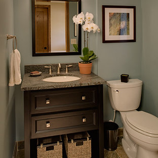 Mid-sized elegant ceramic tile powder room photo in Milwaukee with an undermount sink, black cabinets, granite countertops, a two-piece toilet and blue walls