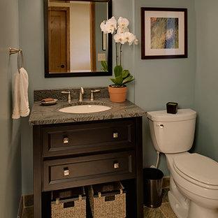 Réalisation d'un WC et toilettes tradition de taille moyenne avec un lavabo encastré, des portes de placard noires, un plan de toilette en granite, un WC séparé, un mur bleu et un sol en carrelage de céramique.