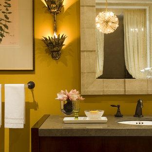 Стильный дизайн: туалет в стиле фьюжн с открытыми фасадами, темными деревянными фасадами, желтыми стенами и столешницей из известняка - последний тренд