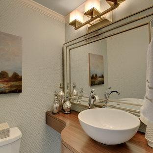 ミネアポリスの小さいトランジショナルスタイルのおしゃれなトイレ・洗面所 (ベッセル式洗面器、木製洗面台、分離型トイレ、ベージュのタイル、セラミックタイル、青い壁、オープンシェルフ、中間色木目調キャビネット、竹フローリング、ベージュの床、ブラウンの洗面カウンター) の写真