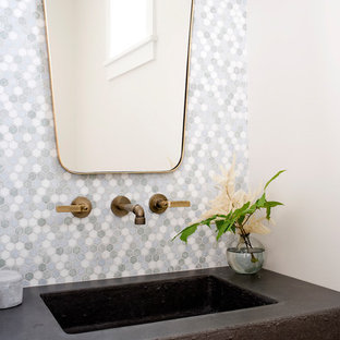 Ispirazione per un bagno di servizio stile marinaro con piastrelle grigie, piastrelle multicolore, piastrelle bianche, piastrelle a mosaico, pareti bianche, lavabo integrato e top nero