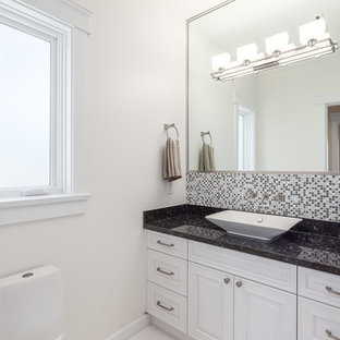 This is an example of a medium sized contemporary cloakroom in Vancouver with white cabinets, a vessel sink, beaded cabinets, multi-coloured tiles, mosaic tiles, white walls, granite worktops and black worktops.