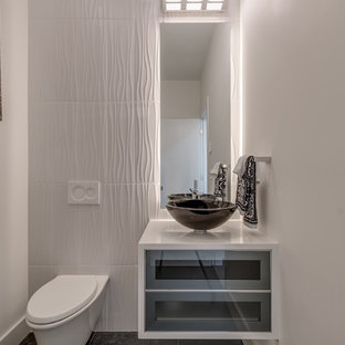 Small modern cloakroom in Vancouver with glass-front cabinets, grey cabinets, a wall mounted toilet, white tiles, porcelain tiles, white walls, ceramic flooring, a vessel sink, engineered stone worktops, grey floors and white worktops.
