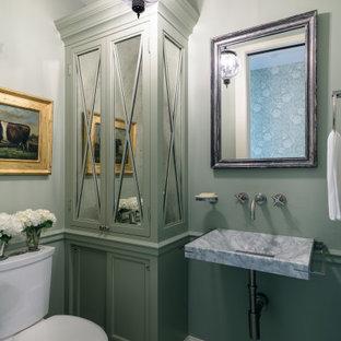 Inspiration pour un petit WC et toilettes traditionnel avec un placard avec porte à panneau encastré, des portes de placards vertess, un WC séparé, un mur vert, un sol en carreaux de ciment, un lavabo suspendu, un plan de toilette en marbre, un sol beige et un plan de toilette gris.