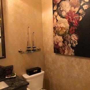 Foto di un piccolo bagno di servizio classico con ante in stile shaker, ante grigie, WC monopezzo, pareti multicolore, pavimento in gres porcellanato, lavabo sottopiano, top in granito e pavimento bianco