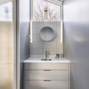 На фото: маленький туалет в современном стиле с плоскими фасадами, серыми фасадами, белой плиткой, керамогранитной плиткой, серыми стенами, бетонным полом, врезной раковиной, столешницей из искусственного кварца, белой столешницей и серым полом с