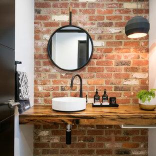 Foto de aseo actual con paredes blancas, lavabo sobreencimera, encimera de madera y encimeras marrones