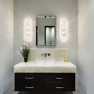 Пример оригинального дизайна: маленький туалет в стиле современная классика с плоскими фасадами, черными фасадами, белыми стенами, полом из керамогранита, настольной раковиной, столешницей из оникса, серым полом и белой столешницей