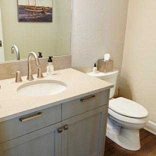 Esempio di un bagno di servizio minimal di medie dimensioni con ante grigie, WC a due pezzi, pareti beige, pavimento in gres porcellanato, lavabo sottopiano, top in quarzo composito e ante con riquadro incassato