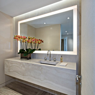 Mittelgroße Moderne Gästetoilette mit flächenbündigen Schrankfronten, beigen Schränken, beigefarbenen Fliesen, beiger Wandfarbe, Unterbauwaschbecken, grauem Boden und beiger Waschtischplatte in Miami