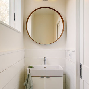 シアトルのカントリー風おしゃれなトイレ・洗面所 (フラットパネル扉のキャビネット、白いキャビネット、白い壁、白い洗面カウンター、独立型洗面台、板張り壁) の写真
