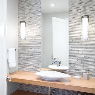 バンクーバーのコンテンポラリースタイルのおしゃれなトイレ・洗面所 (ベッセル式洗面器、オープンシェルフ、淡色木目調キャビネット、木製洗面台、白いタイル、ボーダータイル、白い壁、ベージュのカウンター) の写真