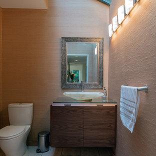 На фото: туалет среднего размера в стиле модернизм с плоскими фасадами, темными деревянными фасадами, раздельным унитазом, бежевыми стенами, полом из травертина, настольной раковиной, стеклянной столешницей и белым полом с