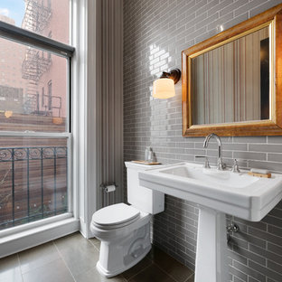 Design ideas for a small traditional cloakroom in New York with a two-piece toilet, grey tiles, a pedestal sink, grey floors, limestone flooring and ceramic tiles.