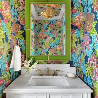 Inspiration pour un WC et toilettes traditionnel avec un placard en trompe-l'oeil, des portes de placard blanches, un mur multicolore, un lavabo encastré, un plan de toilette en marbre et un plan de toilette blanc.