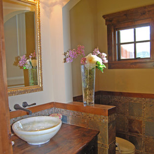 Design ideas for a medium sized rustic cloakroom in Minneapolis with a vessel sink, freestanding cabinets, dark wood cabinets, wooden worktops, multi-coloured tiles, porcelain tiles, beige walls and brown worktops.