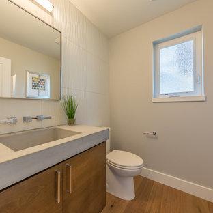 Idee per un grande bagno di servizio minimal con ante lisce, ante marroni, WC a due pezzi, piastrelle grigie, piastrelle in ceramica, pareti grigie, parquet chiaro, lavabo integrato, top in cemento e pavimento marrone