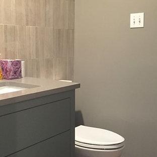 Ispirazione per un piccolo bagno di servizio moderno con lavabo sottopiano, ante lisce, ante grigie, top in quarzo composito, piastrelle grigie, piastrelle in pietra, pareti grigie e pavimento in legno massello medio