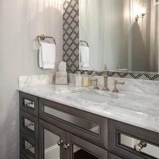 Пример оригинального дизайна: большой туалет в стиле современная классика с стеклянными фасадами, серыми фасадами, разноцветной плиткой, стеклянной плиткой, серыми стенами, паркетным полом среднего тона, врезной раковиной, мраморной столешницей, коричневым полом и белой столешницей