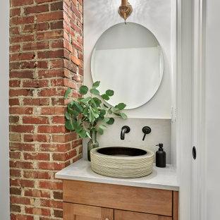 エドモントンの小さいトラディショナルスタイルのおしゃれなトイレ・洗面所 (シェーカースタイル扉のキャビネット、中間色木目調キャビネット、一体型トイレ、白いタイル、セラミックタイル、白い壁、セラミックタイルの床、ベッセル式洗面器、クオーツストーンの洗面台、ベージュの床、白い洗面カウンター、造り付け洗面台、レンガ壁) の写真