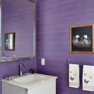 На фото: маленький туалет в современном стиле с фиолетовыми стенами, плоскими фасадами, белыми фасадами, монолитной раковиной и стеклянной столешницей с