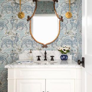 Immagine di un piccolo bagno di servizio chic con ante bianche, WC monopezzo, pareti multicolore, parquet scuro, lavabo sottopiano, top in marmo, pavimento marrone, ante con riquadro incassato e top bianco