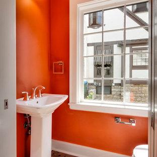 На фото: маленький туалет в классическом стиле с раковиной с пьедесталом, оранжевыми стенами и паркетным полом среднего тона с