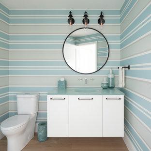 Idée de décoration pour un WC et toilettes marin avec un placard à porte plane, des portes de placard blanches, un WC séparé, un mur multicolore, un sol en bois clair, un lavabo intégré, un plan de toilette en verre et un plan de toilette bleu.