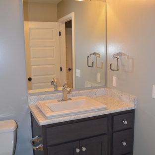 Exemple d'un petit WC et toilettes craftsman avec un placard à porte shaker, des portes de placard en bois sombre, un WC à poser, un mur gris, un sol en linoléum, un lavabo posé et un plan de toilette en stratifié.