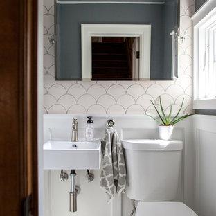 ミネアポリスの小さいトランジショナルスタイルのおしゃれなトイレ・洗面所 (分離型トイレ、白いタイル、セラミックタイル、グレーの壁、大理石の床、壁付け型シンク、白いキャビネット、グレーの床) の写真