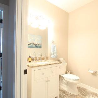 Стильный дизайн: маленький туалет в стиле современная классика с фасадами с утопленной филенкой, белыми фасадами, раздельным унитазом, серыми стенами, полом из винила, врезной раковиной, столешницей из гранита, разноцветным полом и разноцветной столешницей - последний тренд