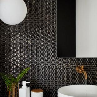 Diseño de aseo minimalista, pequeño, con sanitario de dos piezas, baldosas y/o azulejos negros, baldosas y/o azulejos de vidrio laminado, paredes blancas, lavabo sobreencimera y encimeras negras