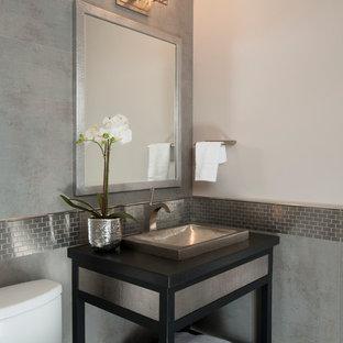Inredning av ett klassiskt toalett, med ett fristående handfat, öppna hyllor, svarta skåp, en toalettstol med separat cisternkåpa, grå kakel, kakel i metall och grå väggar