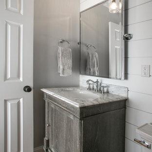 フィラデルフィアの中くらいのエクレクティックスタイルのおしゃれなトイレ・洗面所 (家具調キャビネット、グレーのキャビネット、一体型トイレ、グレーの壁、無垢フローリング、アンダーカウンター洗面器、大理石の洗面台、茶色い床、白い洗面カウンター、独立型洗面台、板張り天井、塗装板張りの壁) の写真